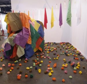 Instalación en la que junto a coloridos pañuelos, aparecen tendidos preservativos llenos de agua