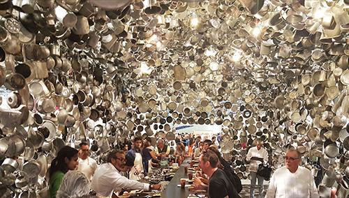 Gente comiendo en el interior de la instalación de Subodh Gupta